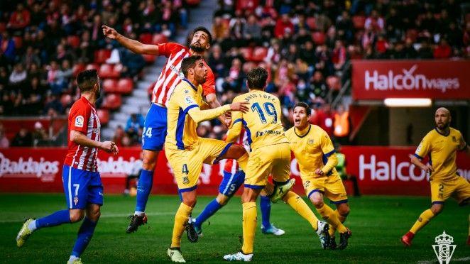 Álex Pérez luchando un balón por alto con la defensa del Alcorcón