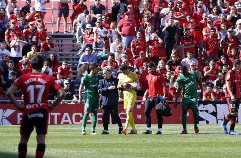 Diego Mariño sale del campo escoltado por el médico del Sporting