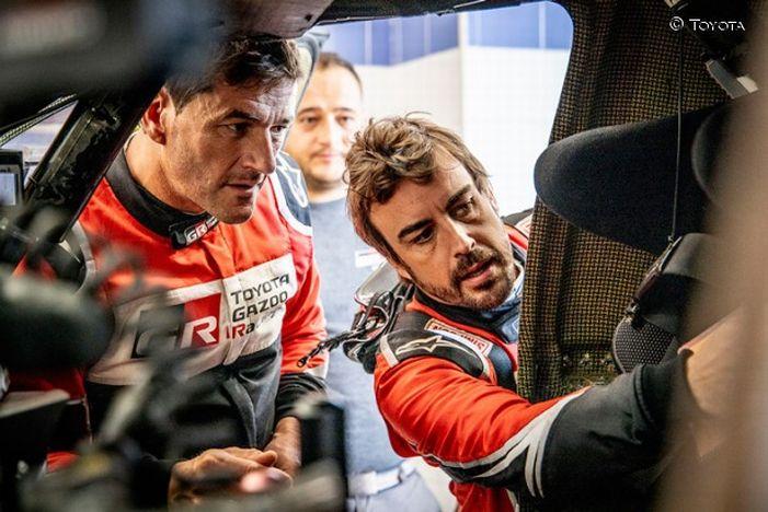 Fernando Alonso y Marc Coma examinando su coche en el Rally de Marruecos